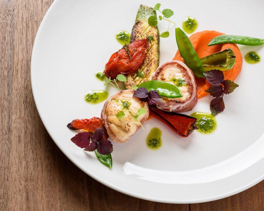 Assiette de Saint-Jacques rôties, tomates confites, purée de carottes, préparée par le chef Laurent Paoli.